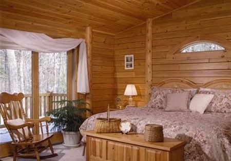 Log home bedroom with eyebrow window