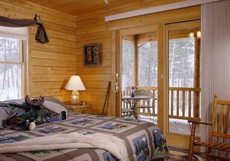 Log home bedroom with doors leading to deck
