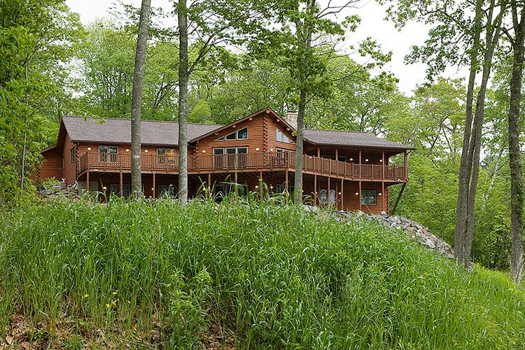 Exterior view of log home with prow front and large deck