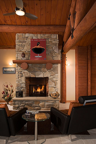 Leather furniture in log home sitting in front of fireplace