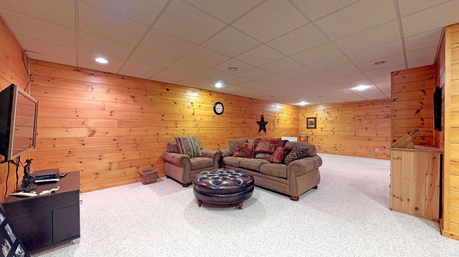 Finished basement of log home with tv and couch