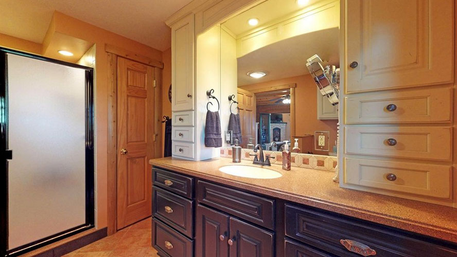 Large bathroom with beautiful vanity and frosted glass shower door