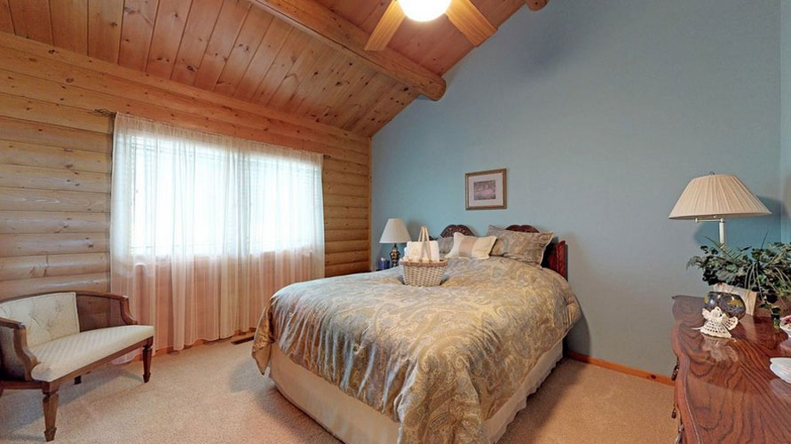 Log home bedroom with drywall painted blue