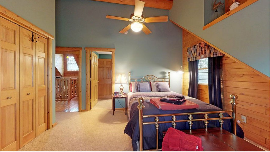 Log home bedroom with sloped ceilings and walls painted blue