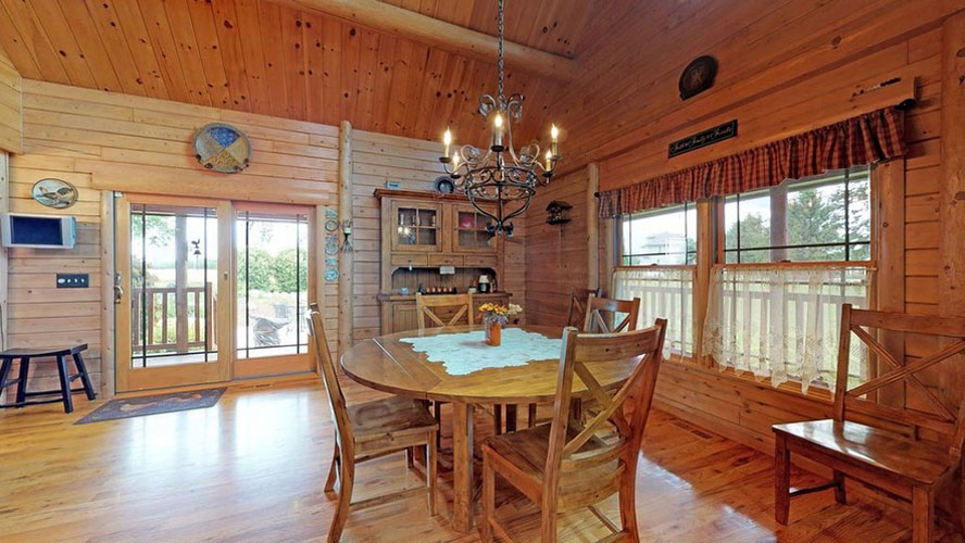 Beautiful Log home dining room with round table and hutch in corner