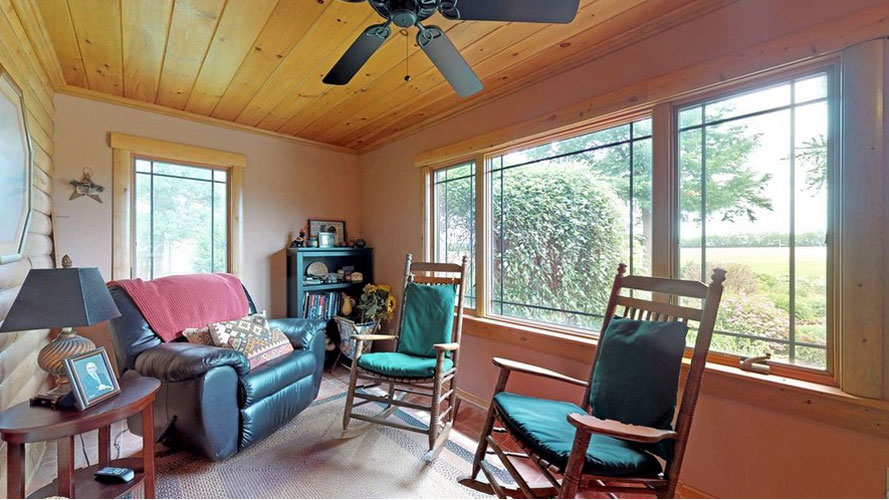 Enclosed porch with two rocking chairs and leather recliner