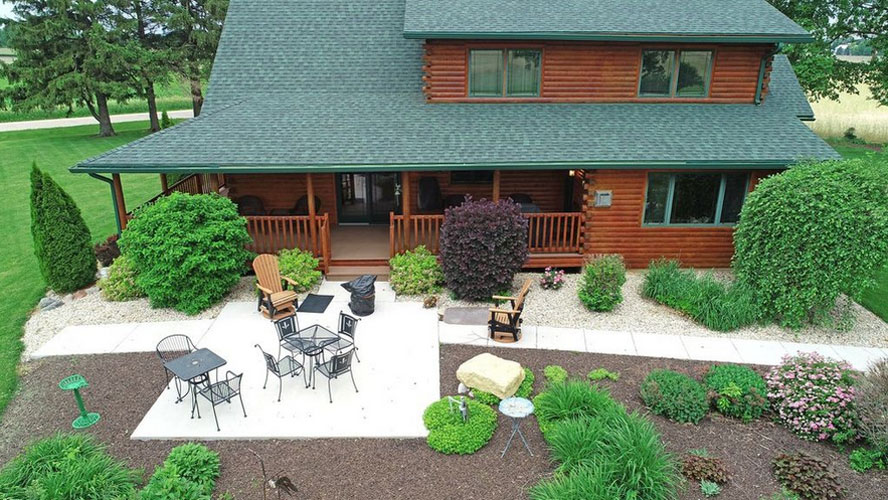 Back of log home with large stone patio and landscaping
