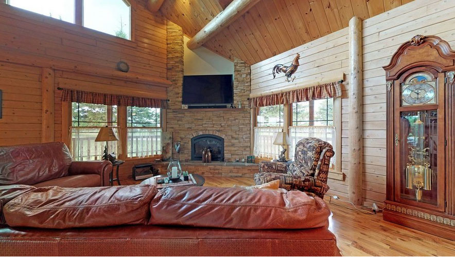 Great Room of Ward Log Home with stone fireplace in the corner