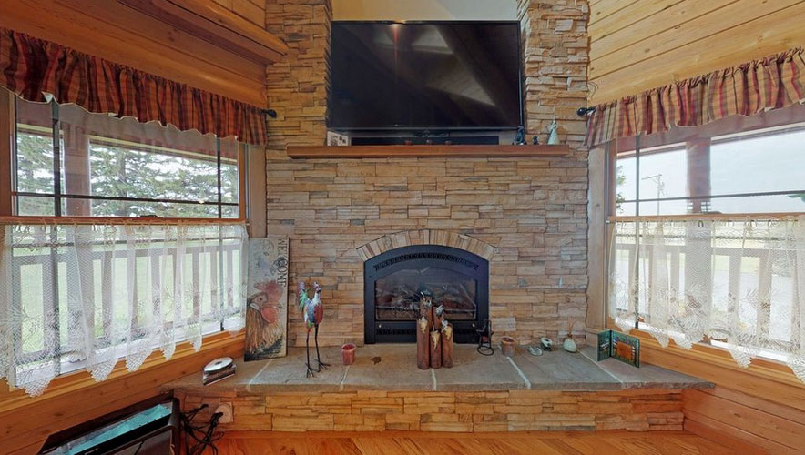 Stone fireplace with TV and windows on each side