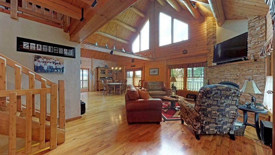 Open living space in log home with stone fireplace and tv mounted above