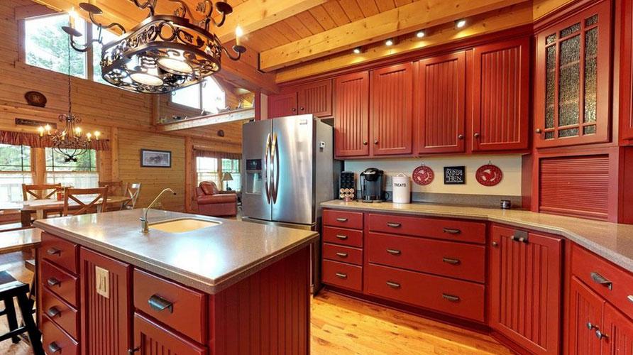 Beautiful Reddish cabinets in log home kitchen