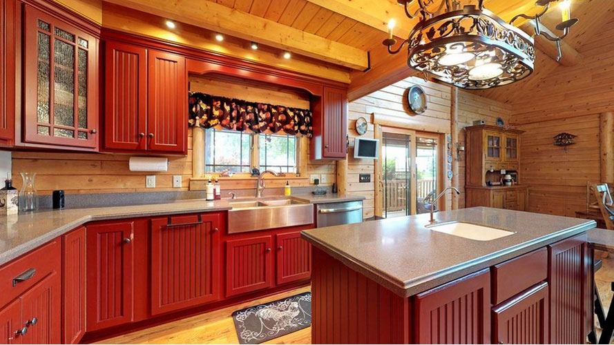 Kitchen with exposed ceiling joist and custom light over island
