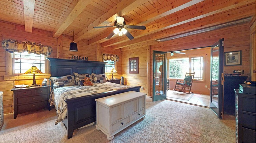 Log home bedroom with frenchdoors going out to enclosed porch