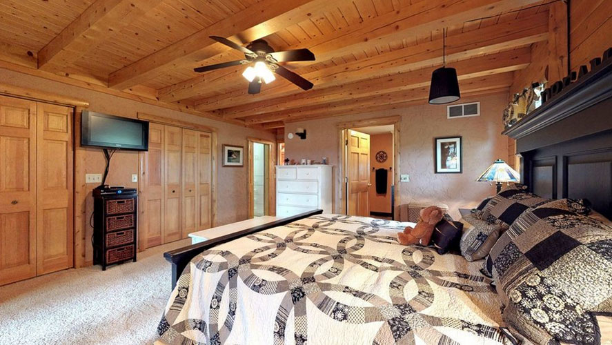 Ward Log Home master bedroom with square exposed beams for ceiling