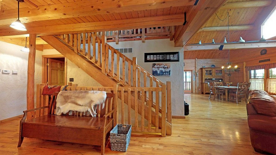 Entryway to log home with wooden bench and log stairs