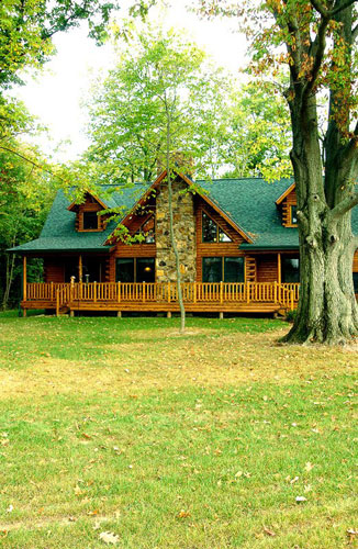 Exterior of log home shaded with trees