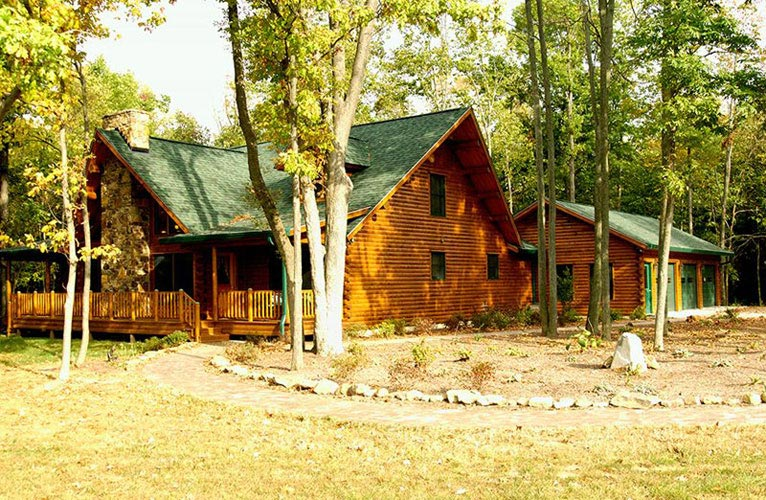 Exterior view of Indy log home surrounded by trees