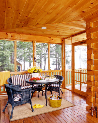 Screened in porch of log home with furniture