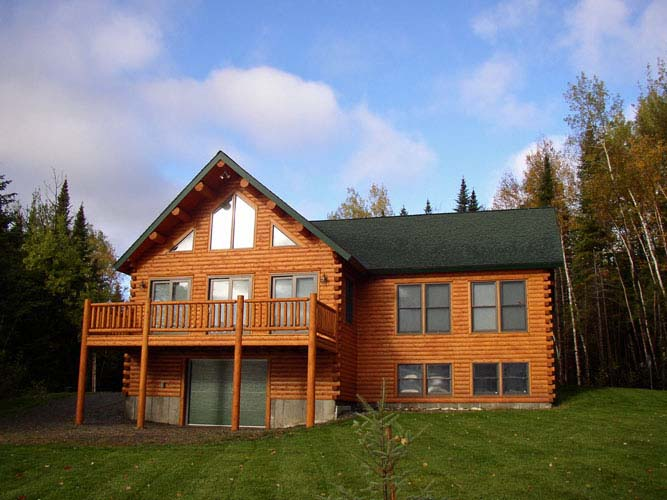 Log home Exterior with daylight basement and deck above