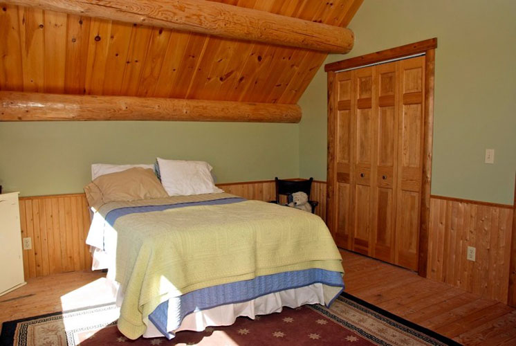 Log Home Hybrid Bedroom with beam ceiling