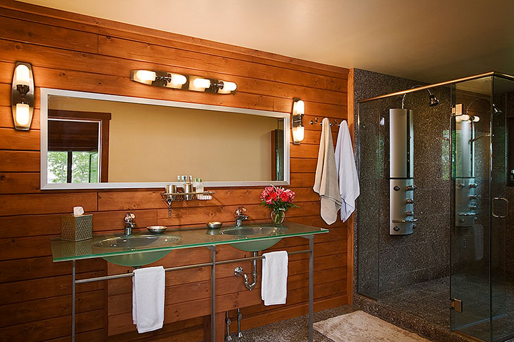 Modern log home bathroom with double sink and glass countertop