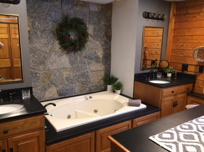 Log Bathroom with double sinks separated by large jet tub