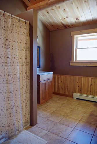 Custom log home bathroom with large walk-in shower and tile floor