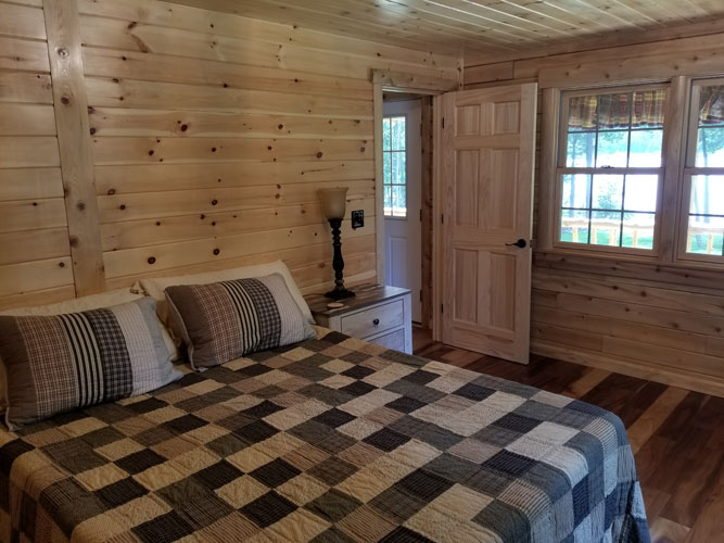 Checkered comforter in bedroom of Musquash log cabin