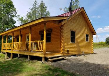 Side view of Ward's Musquash Log Cabin
