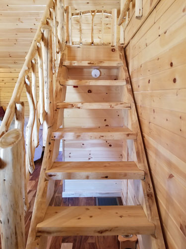 Open stairs leading to loft of Musquash log cabin