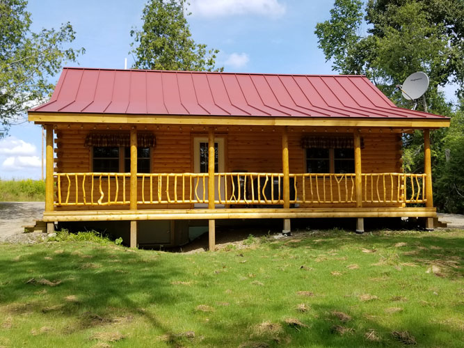 The Musquash Log Cabin with a front porch
