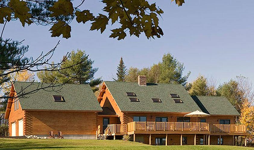 Exterior of log homes with lots of skylights