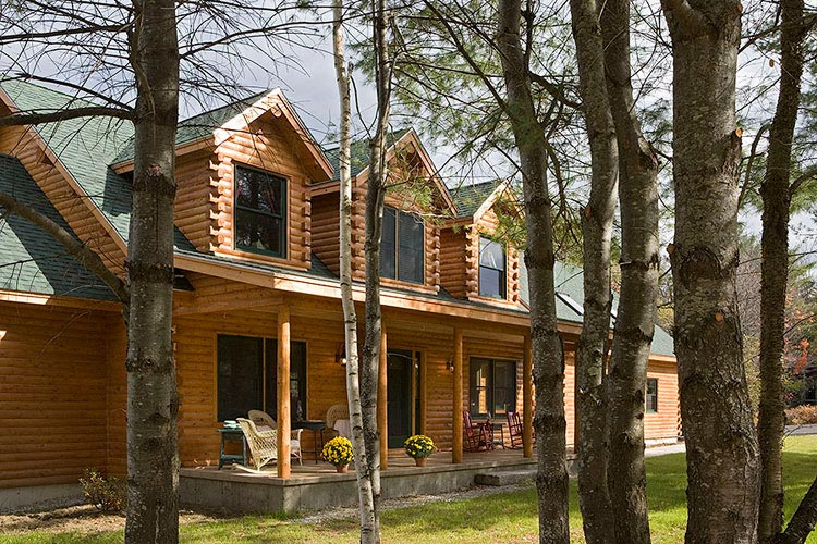 Exterior of log home looking through trees