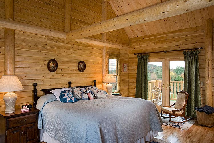 Log home master bedroom with exposed beams