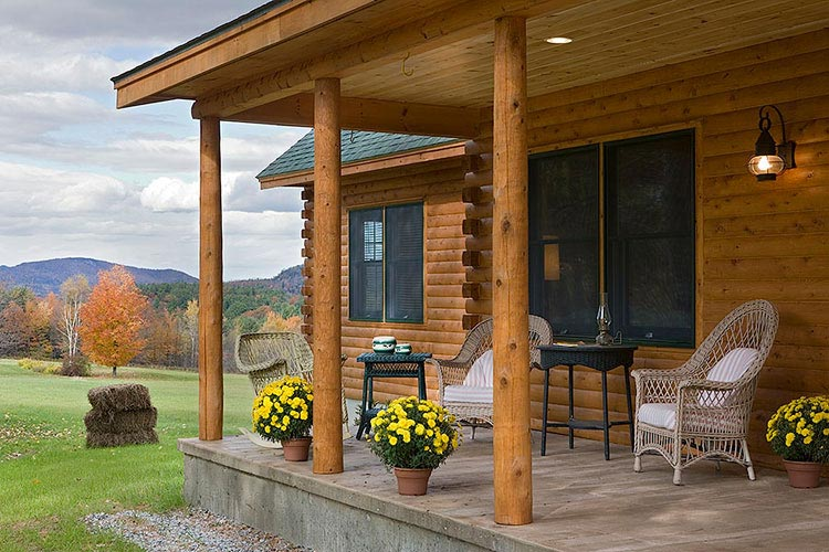 Log home porch on slab with cedar posts